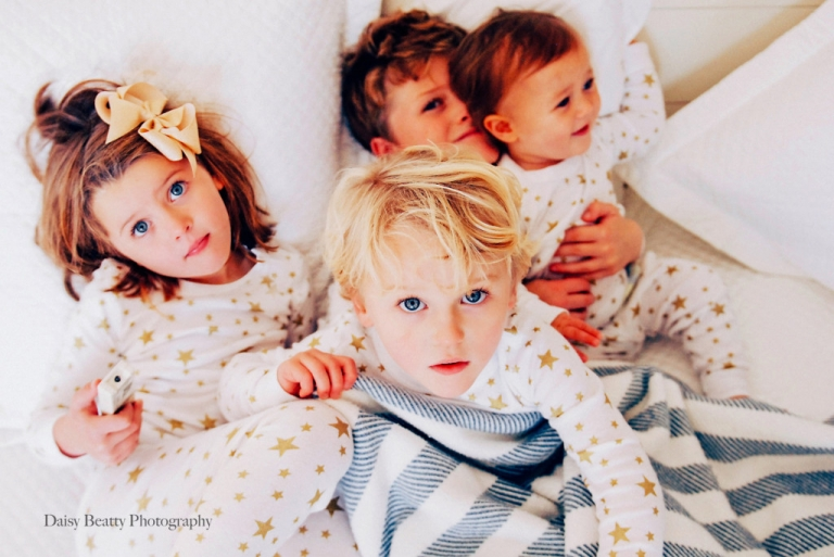 four blue eyed siblings on a bed in greenwich ct by daisy beatty photography