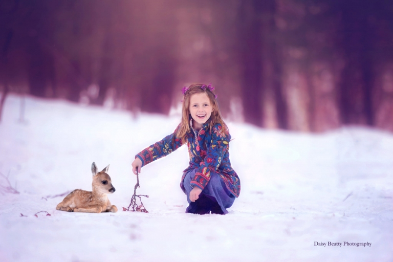 girl and fawn in the woods