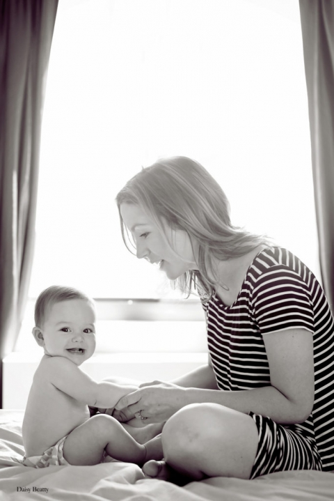 black and white portrait of a mother and her daughter on a bed in manhattan ny by daisy beatty photography