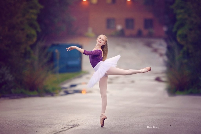 young dancer on pointe in a parking lot by dance photographer manhattan daisy beatty
