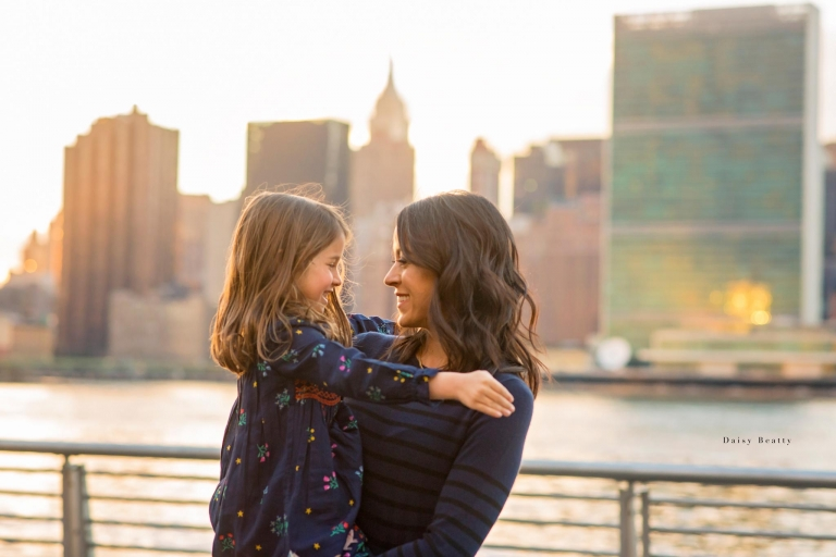glowing mother and daughter at sunset with beautiful light in front of the nyc skyline